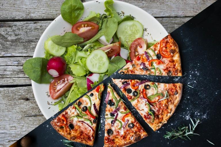 Ein Teller auf der einen Seite ein Salat auf der anderen eine Pizza.