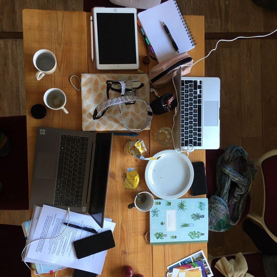 Man sieht mehrere Redakteure bei der Arbeit mit einer Kamera und einem Laptop.