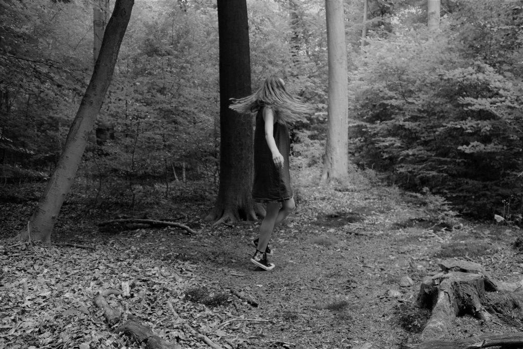 Eine junge Frau steht im Wald und dreht sich