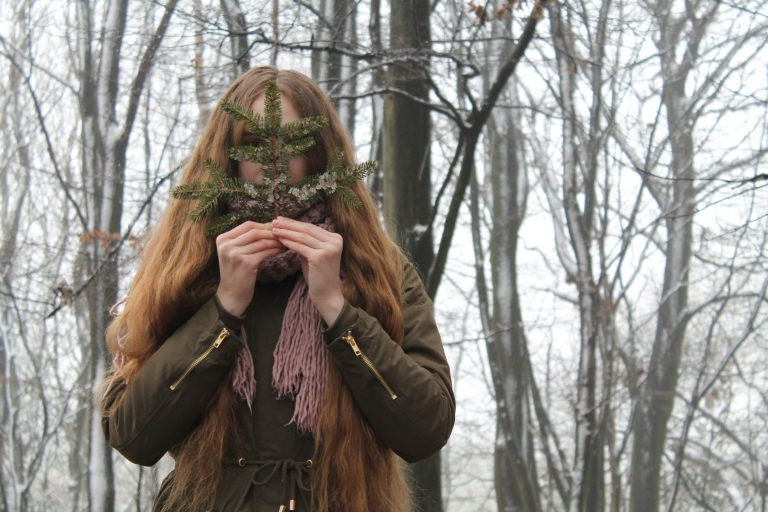 Frau im Wald, die ihr Gesicht mit einem Zweig teilweise verdeckt.